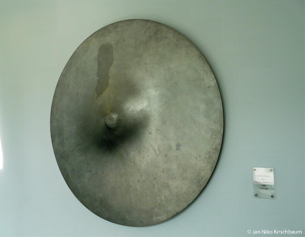 """Der """"Grosse Gong"""" von Friedrich Werthmann. Die kleine gläserne Tafel am rechten Bildrand enthält folgenden Text: """" """"Grosser Gong"""" von Friedrich Werthmann 1986 WVZ 548"""